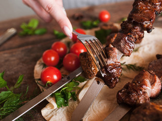 Piece of shish-kebab is taken off from skewer. Grilled meat, field mushrooms and cherry tomatoes on lavash, barbecue and natural food preparing in restaurant, close up picture