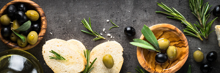 Black and green olives and olive oil on black. Wall mural