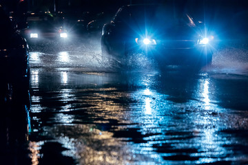 night traffic in city. cars driving through big water puddles with blue headlights.