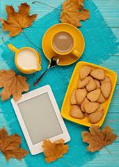 Autumn still life - coffee with a cookie in the form of leaves, an e-book on a blue wooden background.