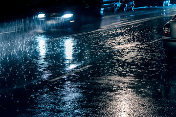 cars driving on street during heavy rain at night, blurred view