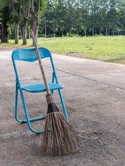 stick broom with blue chair on road