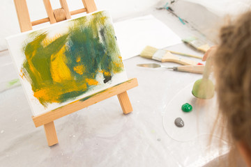 Creative little child painter in working process. Artist workplace, early childhood education, interesting hobby for children, abstract painting