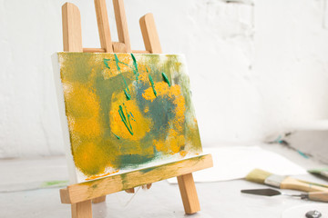 Abstract colorful painting in selective focus. Artistic picture on easel closeup, bright colors, art concept