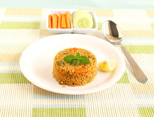 Healthy food quinoa pilaf, and in the background is the tray with raw carrot and cucumber.