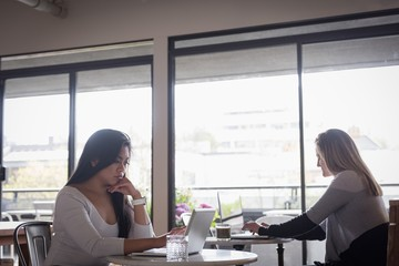 Businesswoman with colleague using laptop at table