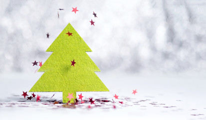 Close up green Christmas tree with sparkling red star falling on white floor at silver background bokeh light,Winter holiday seasonal greeting card