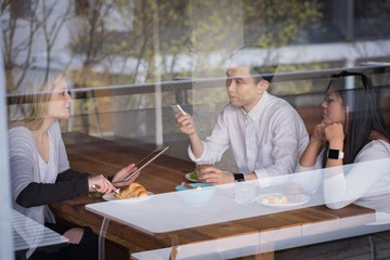Businesswoman with colleagues having food seen through glass