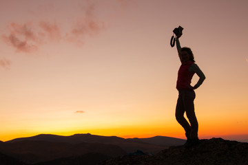Silhouette of happy joyful young attractive woman jumping and having fun at the mountain against the sunset. Freedom, adventure and leisure vacation concept.