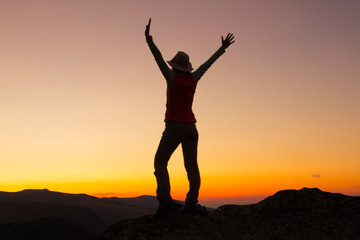 Sunset Silhouette of attractive woman staying and looking happy on top of the mountain. Freedom, adventure and leisure vacation concept.