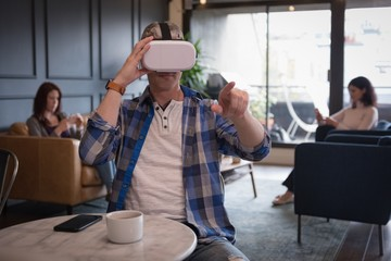 Businessman by colleagues wearing virtual reality simulator at