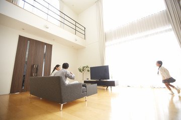 Girl running in a living room, parents watching TV