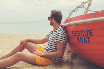 Lifeguard posing with his boat on the beach.