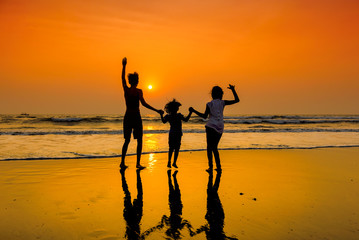 Silhouettes of group of happy children dancing on beach at sunset.