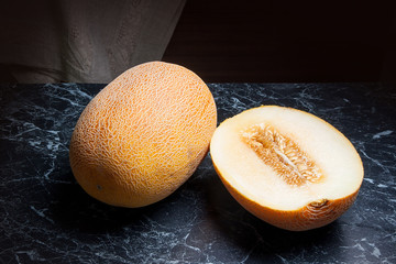 Whole and half honeydew melon fruit on dark marble background.