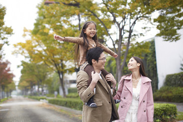 Family of three in park, daughter on father's shoulders