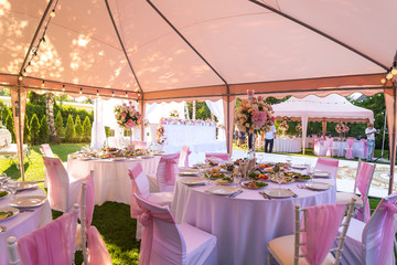 Served round banquet table outdoor in marquee decorated pink flowers and silk