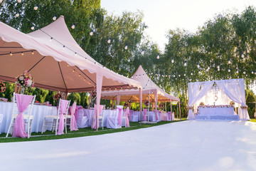 Wedding banquet outdoor in marquees on lawn decorated pink silk, lace and flowers Wall mural