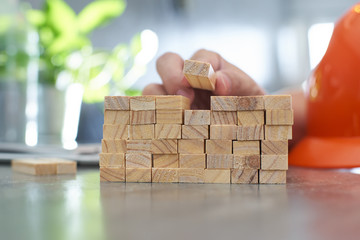 Hand of engineer playing a wood block podiums. Growth in business and goal concept.