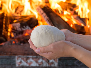 woman hands making fresh raw dough for pizza or bread baking on wooden table against the Burning fireplace. comfort mood concept