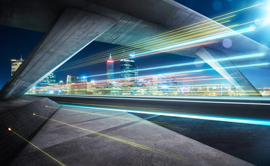 Empty asphalt road under the bridge during the night with light trails and beautiful city skyline background .