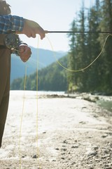 Cropped image of man fishing while standing on riverbank
