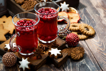 Christmas drink hot cranberry tea and cookies on dark background