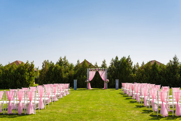 Tender pink and white wedding ceremony decorations on the lawn