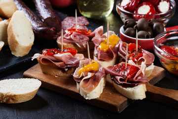 Acrylic Prints Buffet, Bar Spanish tapas with slices jamon serrano and grilled pepper. Also olives, salami, pickled onions, and peppers stuffed with cheese