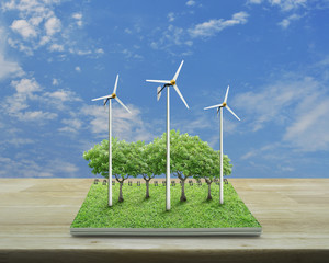 Wind turbines, trees and grass from an open book on wooden table over blue sky with white clouds, Ecological concept