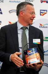 Thierry Vanlancker, CEO of AkzoNobel holds a can of Dulux paint at the opening of the company's new paint factory in Ashington, Britain