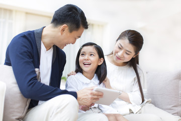 Parents and daughter looking Digital Tablet