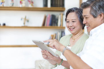 Senior couple looking at digital tablet and laughing