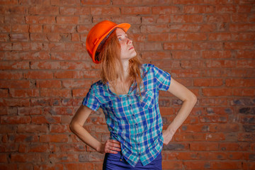 Beautiful and young female architect with orange helmet standing against  brick wall.