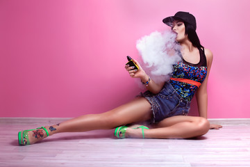 Young sexy woman is vaping. A cloud of vapor. Studio shooting.