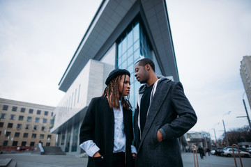 Stylish young couple. African American youth on urban backdrop. Fashionable models on street, sky background, beauty concept