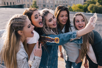 Modern female friendship. Social communication. Girls taking selfie on street