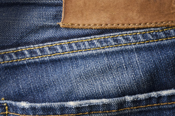 Closeup detail of blank leather jeans label sewed on a blue jeans