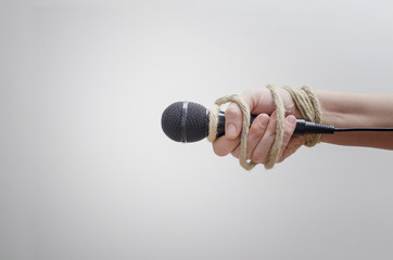 Hand with microphone tied with rope, depicting the idea of freedom of the press, idea of the repression of the mass media or freedom of expression