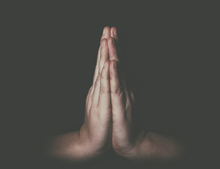 Man hands in praying position low key image