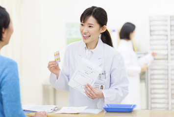 Female pharmacist talking with customer