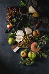 Serving board with sliced camembert cheese and baked bunch of green grapes served with bread, glass of red wine, corkscrew, apples, pears, leaves over black texture background. Top view with space