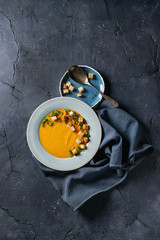 Plate of vegetarian pumpkin carrot soup served with croutons and onion on textile napkin over dark texture background. Top view with space