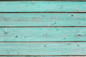 Wooden texture of turquoise color. Old painted fence of boards.