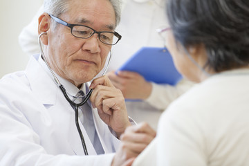 Male doctor examining patient with stethoscope