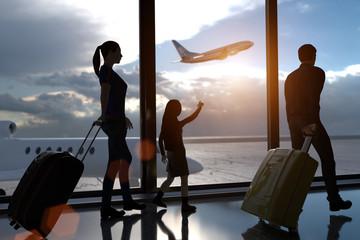 Endlich Urlaub. Eine Familie mit Koffern im Flughafengebäude vor großen Panoramafenster. Draussen die Start und Landebahn. Ein wartendes und ein startendes Flugzeug. Erstellt in 3D.