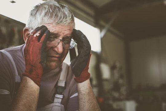 Senior man in workshop. Man having headache after hard work.
