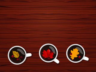 Fragrant autumn tea decorated with autumn leaves and berries on red wooden texture. The view from the top