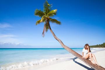 Young girl sitting on a palm tree. Saona island