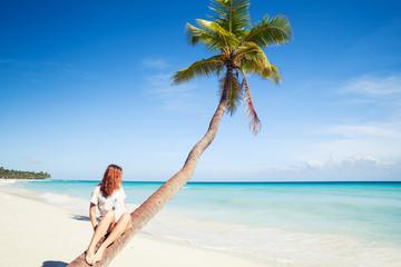 Girl sitting on a palm tree. Saona island beach